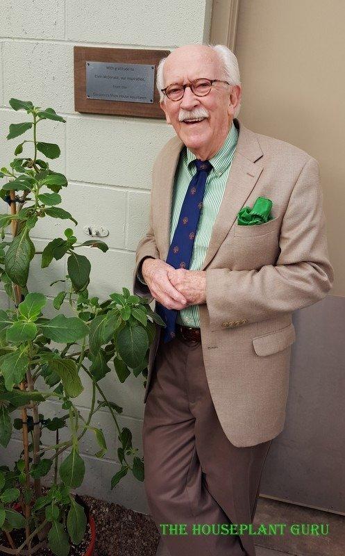 Elvin in the gardener's show house in front of his plaque